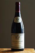 A bottle of Maison Louis Jadot Bourgogne Pinot Noir 2004 red burgundy wine standing on a wooden table top. Backlit backlight back light lit. gray grey background sidelit side light, Maison Louis Jadot, Beaune Côte Cote d Or Bourgogne Burgundy Burgundian France French Europe European