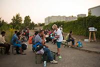 DEU, Deutschland, Germany, Berlin, 13.08.2015: Eine Helferin versorgt wartende Flüchtlinge mit Getränken vor dem Einlass zur Erstregistrierung vor der kurzfristig eingerichteten Notunterkunft im Berliner Stadtteil Karlshorst. Die vom DRK betriebene Erstaufnahmestelle in der Köpenicker Allee soll die Zentrale Aufnahmeeinrichtung für Asylbewerber der LaGeSo in Moabit entlasten.