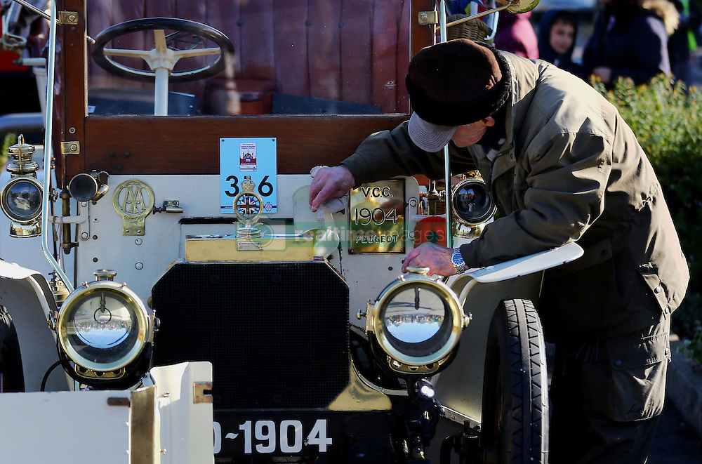 A driver in the Bonhams London to Brighton Veteran Car Run tends to his car during a stop in Crawley, Sussex.