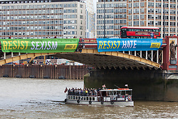 London, UK. 3 June, 2019. Two of five brightly-coloured banners bearing the slogans 'Resist Trump', 'Resist sexism', 'Resist racism', 'Resist hate' and 'Resist cruelty' are dropped on Vauxhall Bridge in view of the US embassy by activists from Amnesty International at the beginning of President Donald Trump's three-day state visit to the UK. Amnesty International has written to Prime Minister Theresa May has written to Theresa May to urge her to raise human rights issues directly with the US President.