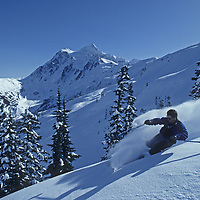 John Bengen skis powder snow on Shukson Arm, near Mount Baker Ski Area, Washington.  Mount Shuksan (in the North Cascades) rises in the backround.
