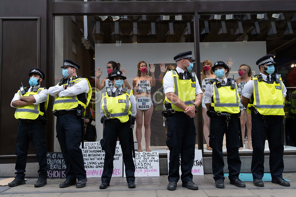 Police officers stand in front of supporters of environmental and Climate Change group Extinction Rebellion , protesting against the ethics of the fashion industry by glueing their hands to the window of H&M on Oxford Street, on 9th September 2020, in London. XR say that the fashion industry produces around 10% of all humanity's carbon emissions, more than all international flights and maritime shipping combined and that over 800,000 tonnes of discarded textile waste annually in the UK.