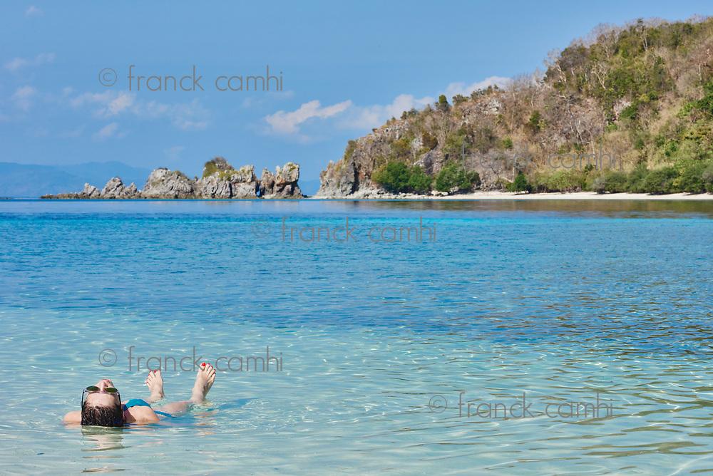 woman tourist sun bathing swimming in Palawan Philippines
