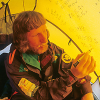 Victor Boyarsky writes the latitude and longitude on his tent at the South Pole, about halfway through the 1989-1990 Trans-Antarctica Expedition.  (The latitude does not read an exact 90 degrees south because he is camped a few hundred meters from the true Pole.