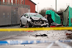 © Licensed to London News Pictures . 08/02/2013 . Salford , UK . Pictured a silver car understood to have been parked when the collision took place whilst behind under a green tarpaulin , the remains of a red Audi on its side with its door lying on the pavement . The scene on Leigh Road where a multi-vehicle pile up killed two , sparked a fire and damaged several cars and houses overnight , causing residents to be evacuated . Greater Manchester Police report seeing a stolen red Audi which they attempted to pursue prior to the crash . Photo credit : Joel Goodman/LNP