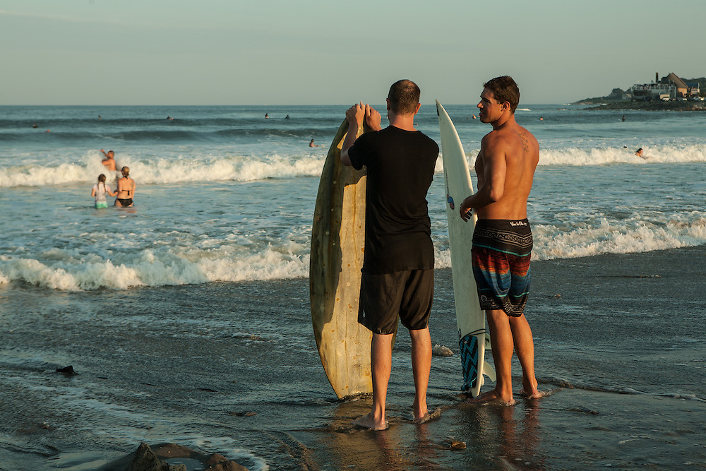 Surfers on the Narragansett Town Beach in the late afternoon.