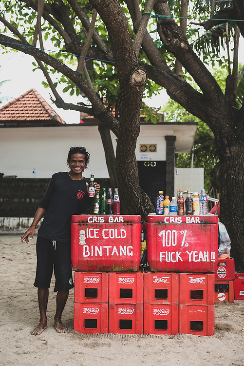 Bali, Indonesia - March 17, 2017: A man stands next to coolers of cold drinks for sale at Kuta Beach in Bali, Indonesia.