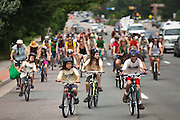 A group of all ages rode bicycles from downtown Boulder, Colorado to the nearby coal-fired Valmont Power Plant to protest its continued operation on July 16, 2011. The protesters planted sunflowers and erected signs on vacant land outside the entrance to the plant.