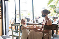 Tulum, Mexico - April 17, 2021: Emily Jeffords and her three-year-old son Elias wait for a drink at Prieto, a cafe on Avenida Tulum.