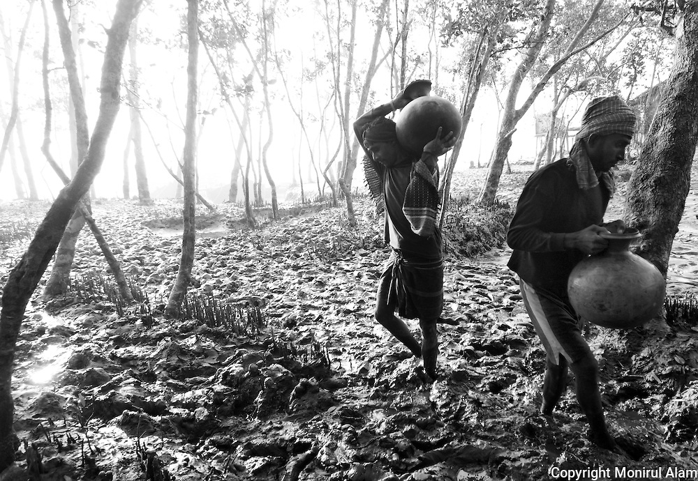 Gabura, Shatkhera. Bangladesh. (2010). Local villagers collect drinking water. Bangladesh ranks first as the nation most vulnerable to the impacts of climate change. Scientists expect rising sea levels to submerge 17 percent of Bangladesh's land and displace 18 million people in the next 40 years.