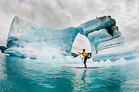 One man on stand up paddle board (SUP) paddles past hole melted in iceberg on Bear Lake in Kenai Fjords National Park, Alaska.