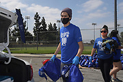 Actor Niko Guardado loads care packages into a car at the Dodger Day Drive-Thru at Belvedere Park, Tuesday, June 30, 2020, in Los Angeles. The event was hosted by The Los Angeles Dodgers Foundation, which distributed food boxes, books, sports equipment, clothing, toys and hygiene supplies to more than 1,000 registered youth from the Boyle Heights, East Los Angeles, La Puente and Monterey Park communities.