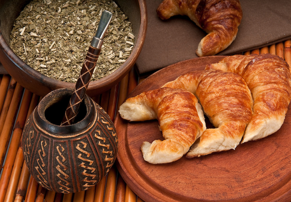 Calabash cup for mate and croissants, with yerba mate in the foreground. Mate is a very popular tradition in Argentina and Uruguay.