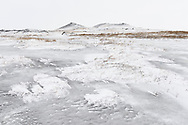 Two small peaks and frozen marshland in the lake Myvatn area on a white and cloudy day in wintertime, Iceland