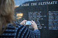 Lori Brewer takes a a photo of the name of her father-in-law William Jackson Brewer etched on the Veterans Memorial Wall during a Veterans Day ceremony at Eastern Kentucky University, Saturday, November 10, 2012. Photo by Chris Radcliffe