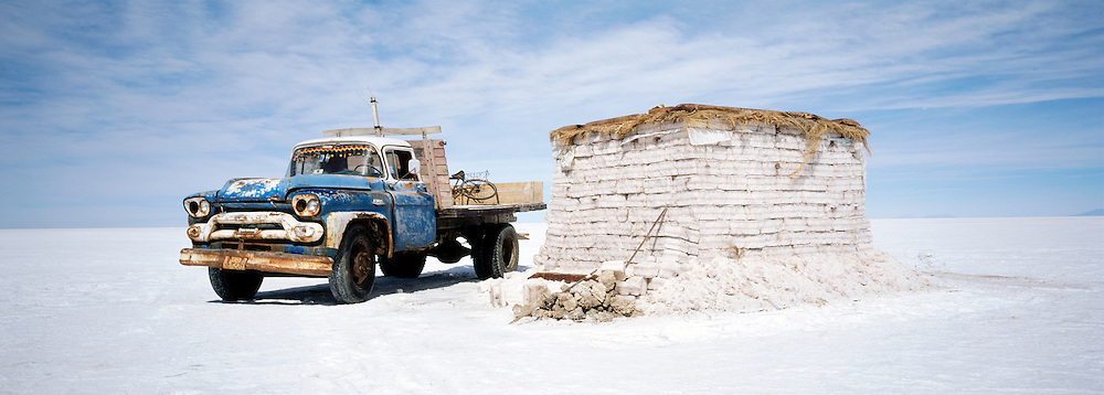 A pick up truck next to stacked up salt bricks on Salar de Uyuni salt flats, Potosi, Bolivia. The Salar de Uyuni are the worlds largest salt flats.