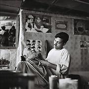 An Afghan barber cuts a customer's beard in Kabul, Afghanistan, Monday, Aug, 21, 2006.