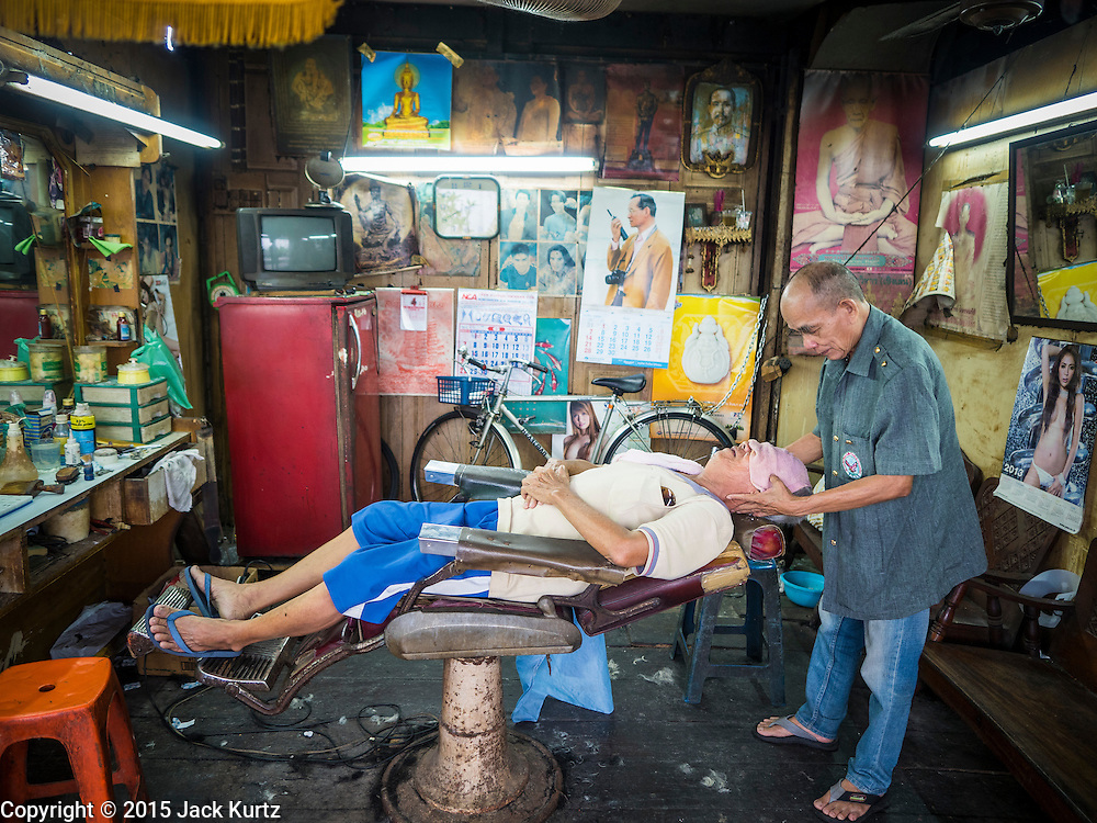 27 JUNE 2015 - BANGKOK, THAILAND:  A barber gives a man a head and shoulder massage after cutting his hair in the Bang Luang neighborhood of the Thonburi section of Bangkok. The Bang Luang neighborhood lines Khlong (Canal) Bang Luang in the Thonburi section of Bangkok on the west side of Chao Phraya River. It was established in the late 18th Century by King Taksin the Great after the Burmese sacked the Siamese capital of Ayutthaya. The neighborhood, like most of Thonburi, is relatively undeveloped and still criss crossed by the canals which once made Bangkok famous. It's now a popular day trip from central Bangkok and offers a glimpse into what the city used to be like.       PHOTO BY JACK KURTZ