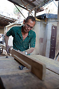 Cuban man wearing glasses in a workshop cutting wood on a table saw, sawdust.