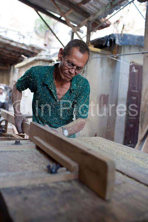 Cuban man wearing glasses in a workshop cutting wood on a table saw, sawdust.