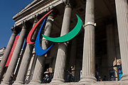 "The Paralympic agito logo hangs between the pillars of the National (Art) Gallery on the north side of Trafalgar Square during the London games which took place between 29 Aug - 9 Sept 2012. The tall pillars act as a backdrop of this famous gallery in central London. The Paralympic symbol consists of three agitos, coloured red, blue and green, the three colours that are most widely represented in national flags around the world. These agitos, coloured red, blue, and green, encircle a single point, on a white field. The agito (""I move"" in Latin) is a symbol of movement in the shape of an asymmetrical crescent. The Paralympic symbol was created by the Scholz & Friends agency and approved in April 2003."