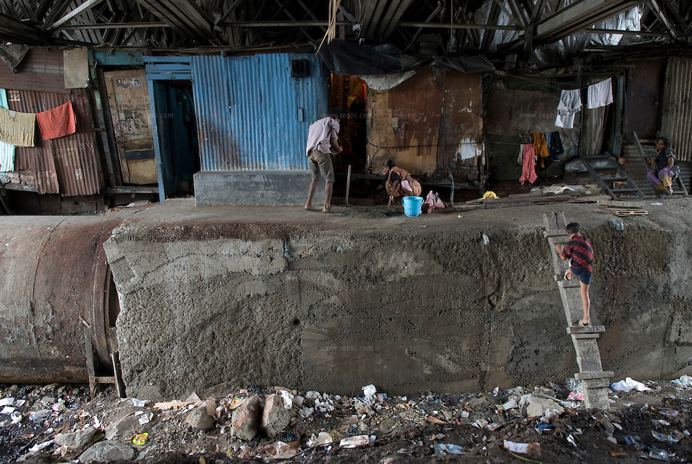 a couple repair the family home, stacked between the water pipe that carries water to mumbai and a bridge above.