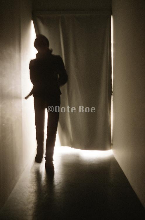 Person leaving a dark hall