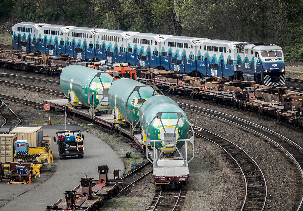 Boeing 737 fuselages wait in a Seattle railroad yard for delivery to the Boeing Renton Assembly plant in Renton, WA.  4/16/19.  A Sound Transit Sounder commuter train passes, above.