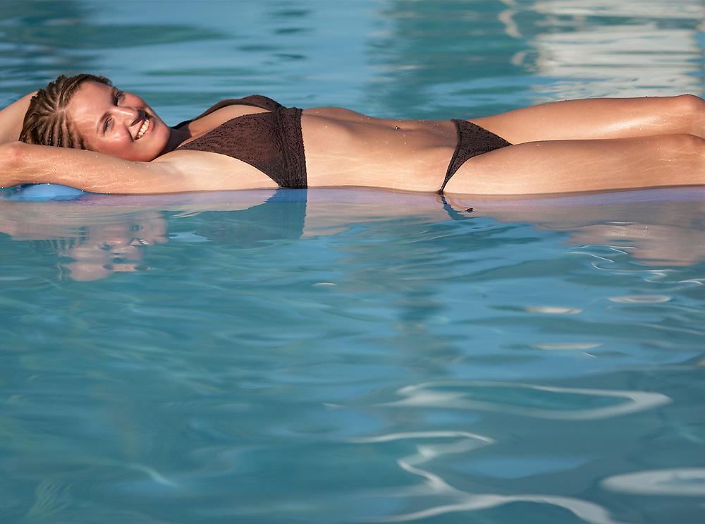 Smiling woman wearing a bikini, sunbathing and relaxing in pool