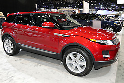 "08  February 2013: 2013 Range Rover Evoque 5 door Sport Utility Vehicle (SUV). Chicago Auto Show, Chicago Automobile Trade Association (CATA), McCormick Place, Chicago Illinois<br /> <br /> 2013 LAND ROVER RANGE ROVER EVOQUE: Introduced for 2012, the Range Rover Evoque targets a new generation of Range Rover enthusiasts, starting with a bold, dynamic profile and distinctive taper to the ""floating"" roofline. It maybe the smallest, lightest and most fuel-efficient Range Rover ever produced, but the 2013 Range Rover Evoque stays true to the core brand values by providing premium levels of craftsmanship, luxury, performance and multi-terrain capability. Offered in a choice of coupe and five-door body styles, the Evoque is available in three trim levels, each with its own distinctive character. For cool and contemporary, there is the Evoque ""Pure,"" with aluminum alloy roof. Then there is the luxurious ""Prestige"" and the bold and sporting ""Dynamic,"" with standard panoramic laminated glass roof. All models provide five passenger seating, while the coupe exclusively offers a package that uses individual rear seats, for a 2+2 cabin. When it comes to hauling groceries or sports gear, the Range Rover Evoque offers a wide, deep cargo area. With the rear seats folded, the five-door provides 51 cu.-ft. of space, the coupe slightly less at 47.6 cu.-ft. All Range Rover Evoque models are powered by a 2-liter, 240 horsepower direct-injected turbocharged four-cylinder engine, which is teamed to a six-speed automatic transmission and a full-time, intelligent four-wheel drive system. New this year is a revised front grille design that includes the black Land Rover logo, new contrast roof color as a stand-alone option, and to aid in exploring unmapped areas, Land Rover Off-Road navigation has been added to the Range Rover Evoque for 2013."