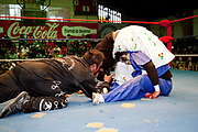 Female wrestler with male opponent in head lock and referee in the ring. Lucha Libre wrestling origniated in Mexico, but is popular in other latin Amercian countries, including in La Paz / El Alto, Bolivia. Male and female fighters participate in the theatrical staged fights to an adoring crowd of locals and foreigners alike.