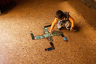 A small boy touches a swastika on the floor of a Tibetan Buddhist monastery in Shigatse, Tibet (China).  The swastika is a well known symbol of peace and tolerance in Asia, quite different from its perception in the western world.