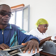 CAPTION: The PWD community faces discrimination on a daily basis. Access to schools, jobs and public services is often limited. Responding to adult literacy challenges by teaching Braille helps ACAMO members to develop active voices for dialogue with the government. It also serves as a method of rehabilitation, building hope for participants that they will eventually be able to return to regular employment and be re-integrated into the mainstream workforce. LOCATION: Lulimile Village, Lichinga, Niassa Province, Mozambique. INDIVIDUAL(S) PHOTOGRAPHED: Saide Rajabo (left) and Anissa Bernado Binamur (right).