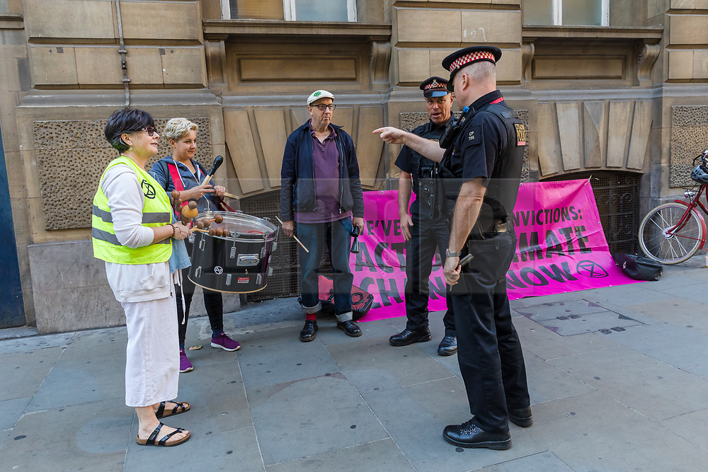 © Licensed to London News Pictures. 13/09/2019. London, UK. Police speak to members of Extinction Rebellion as they play musical instruments outside City of London Magistrates court this morning. Over 50 defendants from across the UK are appearing at City of London Magistrates court in London today, charged with being public assembly participants failing to comply with police conditions related to Extinction Rebellion climate change protests in London. Photo credit: Vickie Flores/LNP