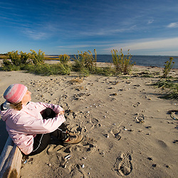 A woman on the beach in fall.  Griswold Point, Old Lyme, Connecticut. The Nature Conservancy's Griswold Point Preserve.   Mouth of the Connecticut River at Long Island Sound.