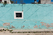 A blue painted wall decaying under the desert sun in the ghost town of Mineral de Pozos, Guanajuato, Mexico. The town, once a major silver mining center was abandoned and left to ruin but has slowly comeback to life as a bohemian arts community.