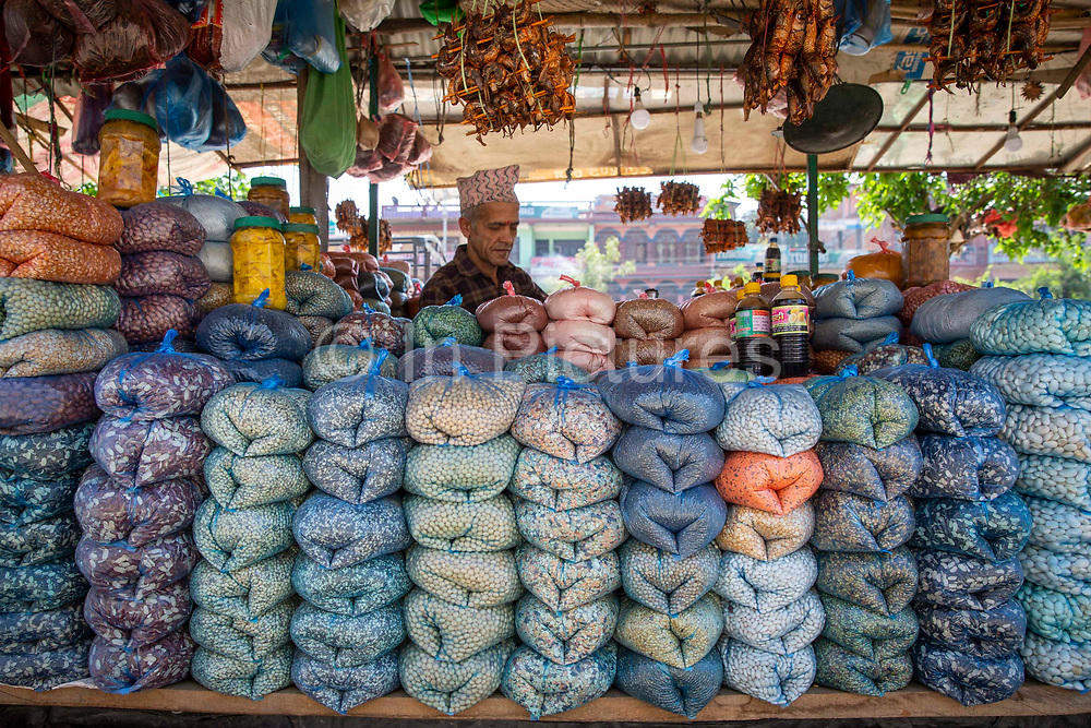 A shopkeeper selling pulses and dried spices in the bazaar outside Malekhu Petrol station on the 3rd of March 2020 in Malekhu,  Benighat region, Nepal.  Malekhu is a small town situated between the river Trishuli and the H04 Kathmandu to Pokhara road in the Benighat region of Nepal.