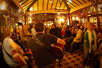 People listening to a traditional Irish band play in the Temple Bar in Dublin, Ireland