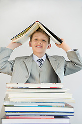 Portrait of boy with stack books, holding one book over his head as roof