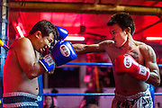 """26 SEPTEMBER 2014 - PATTAYA, CHONBURI, THAILAND: Muay Thai boxers put on a demonstration fight in a beer bar in Pataya. Pataya, a beach resort about two hours from Bangkok, has wrestled with a reputation of having a high crime rate and being a haven for sex tourism. After the coup in May, the military government cracked down on other Thai beach resorts, notably Phuket and Hua Hin, putting military officers in charge of law enforcement and cleaning up unlicensed businesses that encroached on beaches. Pattaya city officials have launched their own crackdown and clean up in order to prevent a military crackdown. City officials have vowed to remake Pattaya as a """"family friendly"""" destination. City police and tourist police now patrol """"Walking Street,"""" Pattaya's notorious red light district, and officials are cracking down on unlicensed businesses on the beach.     PHOTO BY JACK KURTZ"""