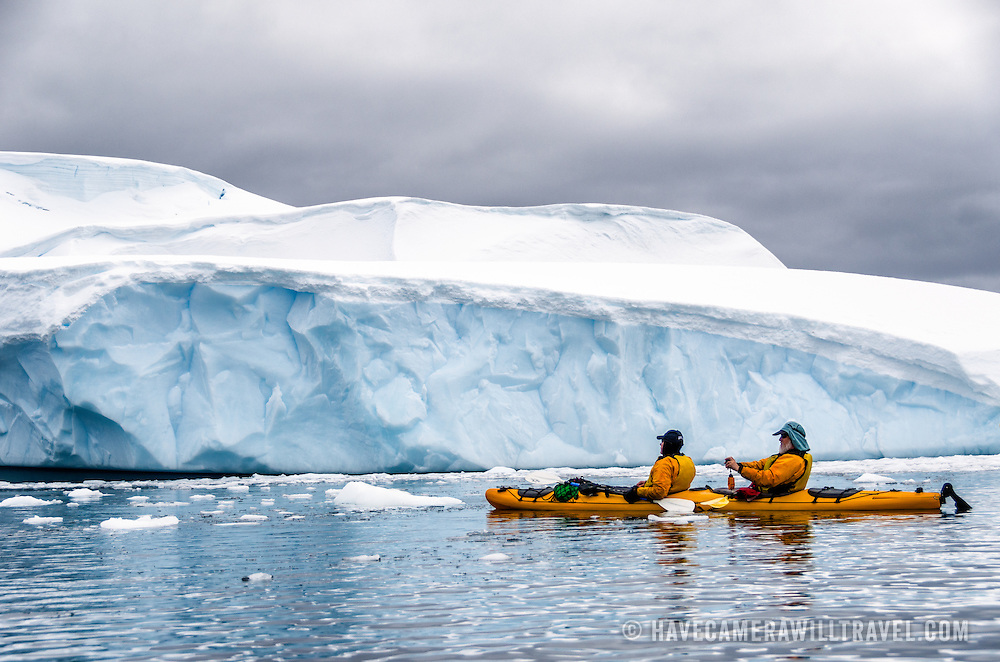 Two kayakers in a tandem kayak paddle along the shore lined with steep glaciar cliffs near Melchior Island on the Antarctic Peninsula.