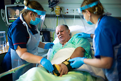 © Licensed to London News Pictures . 11/02/2021. Wythenshawe , UK . Two members of ward staff help patient KEVIN CRAMPTON (59) reposition himself in his bed . Kevin has been ventilated and proned on the route to recovery from Coronavirus . Covid positive patients are treated for the effects of Coronavirus in Wythenshawe's A1 Respiratory Ward . Photo credit : Joel Goodman/LNP
