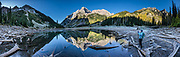 The Maroon Bells reflect in Crater Lake. The Maroon Bells are two adjacent peaks of the Elk Mountains: Maroon Peak 14,163 feet on left, seen behind North Maroon Peak 14,019 feet, in Maroon Bells-Snowmass Wilderness of White River National Forest. The mountains are on the border between Pitkin County and Gunnison County, 12 miles southwest of Aspen, in Colorado, USA. This image was stitched from multiple overlapping photos.
