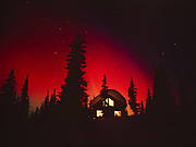 Brilliant red aurora behind cabin at Colorado Lake, geomagnetic storm during the early morning hours of March 31, 2001, Broad Pass, Alaska.