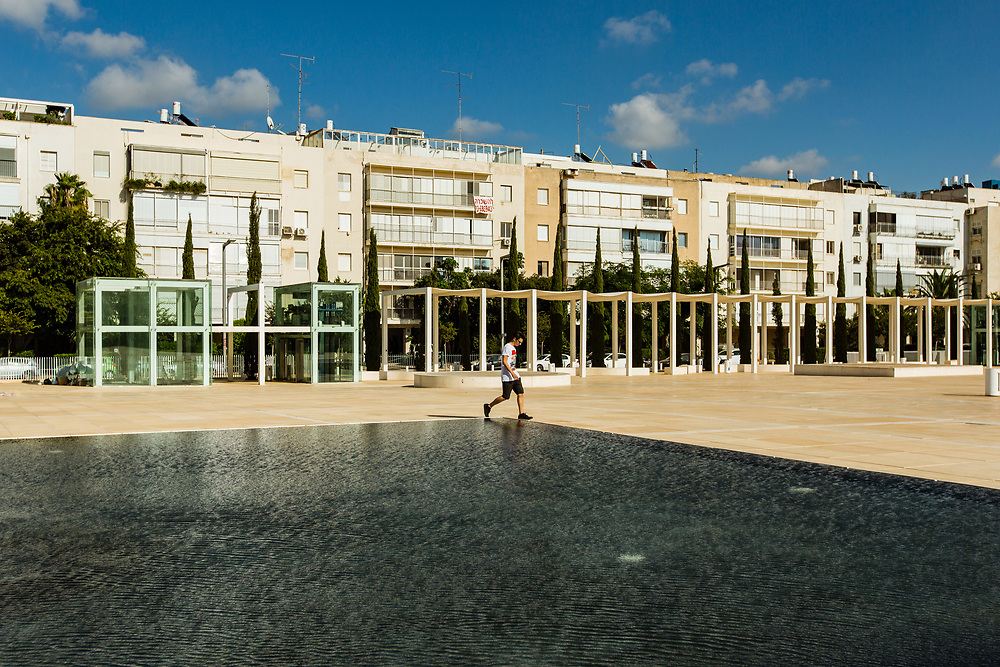 A person walks past a pool by the Charles Bronfman Auditorium (Heichal Hatarbut) at Habima Square (or Culture Square) in Tel Aviv's Lev Hair neighborhood