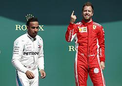 Ferrari's Sebastian Vettel (right) celebrates winning the 2018 British Grand Prix alongside Mercedes' Lewis Hamilton who finished second at Silverstone Circuit, Towcester.