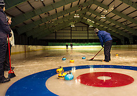 Dick Pease sweeps his blue teams stone thrown by Jim Bobotas during the first night of curling at the Arthur Tilton Ice Rink with the Gilford Parks and Rec on Thursday.  (Karen Bobotas/for the Laconia Daily Sun)