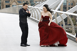 © Licensed to London News Pictures. 04/05/2021. London, UK. A Chinese wedding couple react to the windy conditions as they pose for photographs on the Millennium footbridge over the River Thames in the City of London. High winds and heavy rain are affecting parts of the UK today. Photo credit: Peter Macdiarmid/LNP