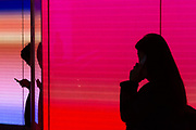 Silhouettes of young people using mobile phones in front of a colourful illuminated wall in Shibuya, Tokyo, Japan, Friday December 14th 2018
