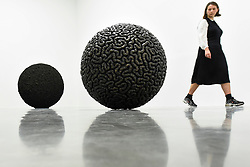 """© Licensed to London News Pictures. 11/09/2019. LONDON, UK. A staff member views (L) """"Dark Matter"""", 2019, and (R) """"Inside Out"""", 2019. Preview of """"Remains to be Seen"""", a new exhibition by Mona Hatoum at White Cube gallery in Bermondsey.  This is the first presentation of her work since Tate Modern in 2016.  The show runs 12 September to 3 November 2019.  Photo credit: Stephen Chung/LNP"""